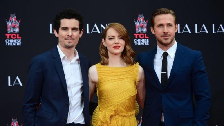 Actors Emma Stone and Ryan Gosling pose with writer and director Damien Chazelle (L) at their Hand and Foot prints ceremony in front of the TCL Chinese Theater in Hollywood on December 7, 2016 ahead of the release of the film LA LA Land set for December 9. / AFP / Frederic J. BROWN        (Photo credit should read FREDERIC J. BROWN/AFP/Getty Images)